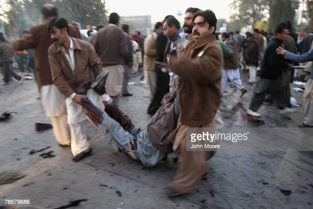 A wounded supporter of former Prime Minister Benazir Bhutto is carried away from the scene of an assassination attack on Bhutto following a campaign...