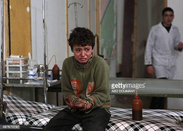 A wounded Syrian boy cries at a makeshift hospital following a reported air strike by government forces in the rebelheld area of Douma east of the...