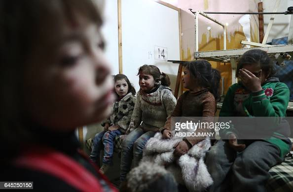 TOPSHOT Wounded Syrian girls cry as they wait to receive treatment at a makeshift hospital following reported government airstrike on the rebelheld...