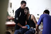 A wounded Syrian receives treatment at a makeshift hospital following a reported regime air raid in the besieged rebel bastion of Douma northeast of...