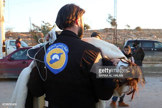 TOPSHOT A wounded Syrian who was evacuated from rebelheld neighbourhoods in the embattled city of Aleppo is carried by a medic as she arrives in the...
