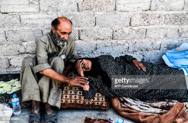 TOPSHOT Wounded Syrians rest on the front line in eastern Raqa on July 13 during an offensive to retake the city from Islamic State group fighters...