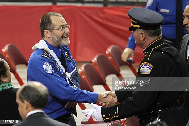 Wounded Transportation Security Administration officer James Speer shakes hands with a Los Angeles Airport Police Honor Guard officer at a public...