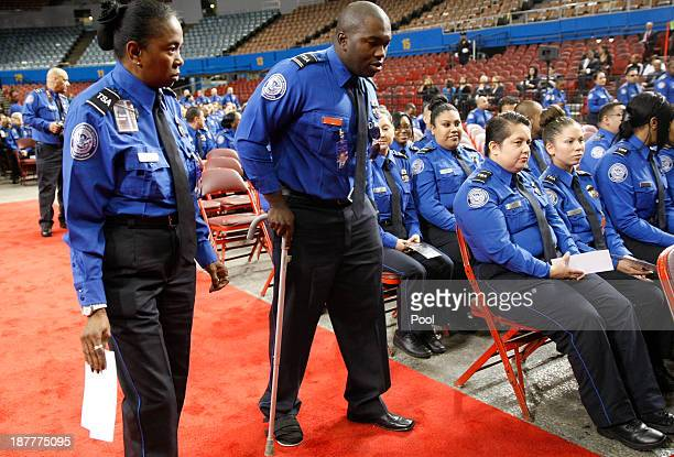 Wounded TSA Officer Tony Grigsby is escorted to fix seat by fellow officer Faye May prior to a public memorial for Transportation Security...