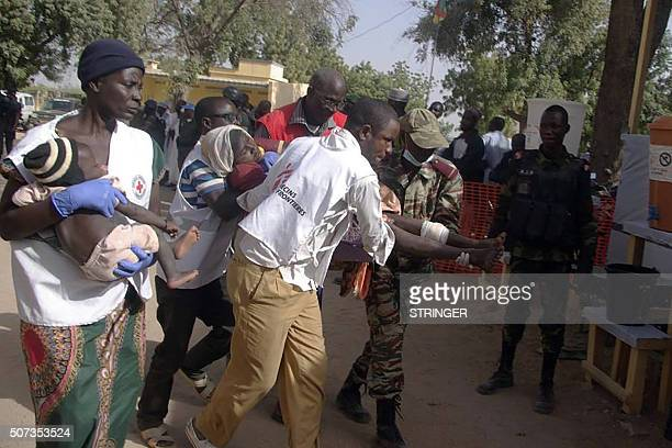 A wounded woman and child are carried by rescuers on January 28 2016 in Mora following suicide attacks in the border city of Kerawa northern Cameroon...