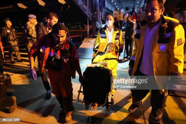 TOPSHOT A wounded woman from the latest explosion in Mogadishu is escorted on a wheelchair by Turkish emergency workers to receive treatment in a...