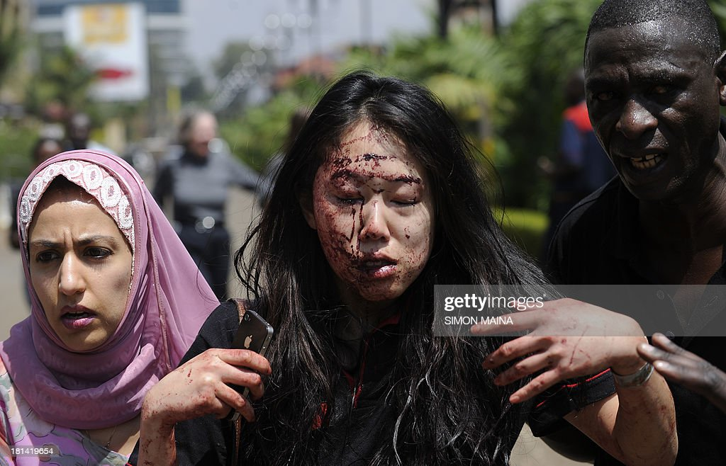 A wounded woman is helped to safety after masked gunmen stormed an upmarket mall and sprayed gunfire on shoppers and staff, killing at least six on September 21, 2013 in Nairobi. The Gunmen have taken at least seven hostages, police and security guards told an AFP reporter at the scene.
