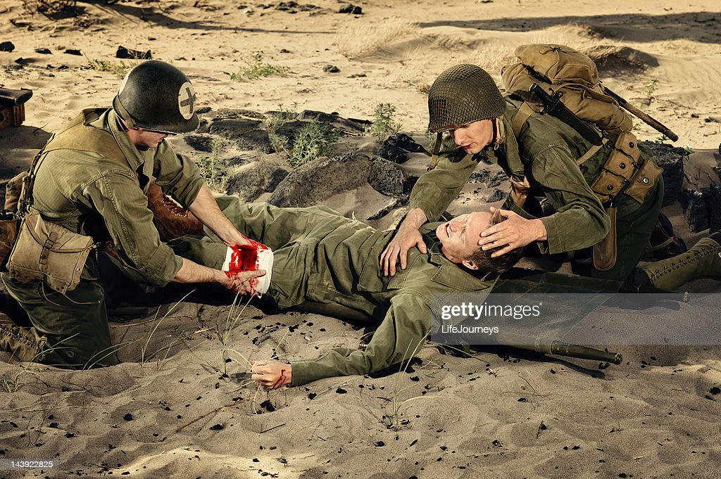 Wounded WWII Soldier Being Triaged By Medic And Commrad : Stock Photo