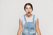 Wow! Portrait of  cute woman with shocked facial expression. Studio shot, gray wall