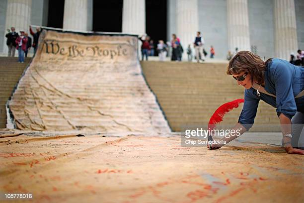 A wpman signs a giant banner printed with the Preamble to the United States Constitution during a demonstration against the Supreme Court's Citizens...
