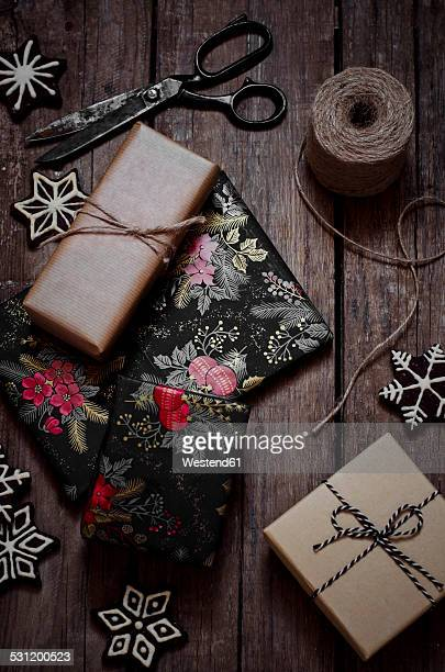 Wrapped christmas gifts, decoration, scissors and string on wooden table