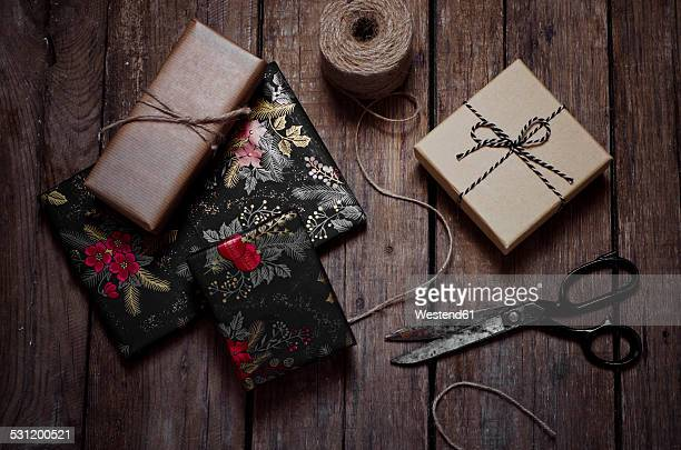 Wrapped christmas gifts, scissors and string on wooden table