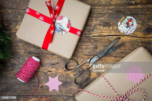 Wrapped Christmas presents and scissors on dark wood