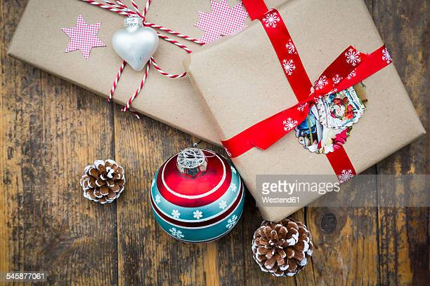 Wrapped Christmas presents, Christmas bauble and fir cones on dark wood