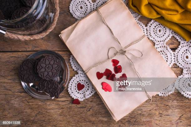Wrapped empty old paper and cocoa cookies on wooden table
