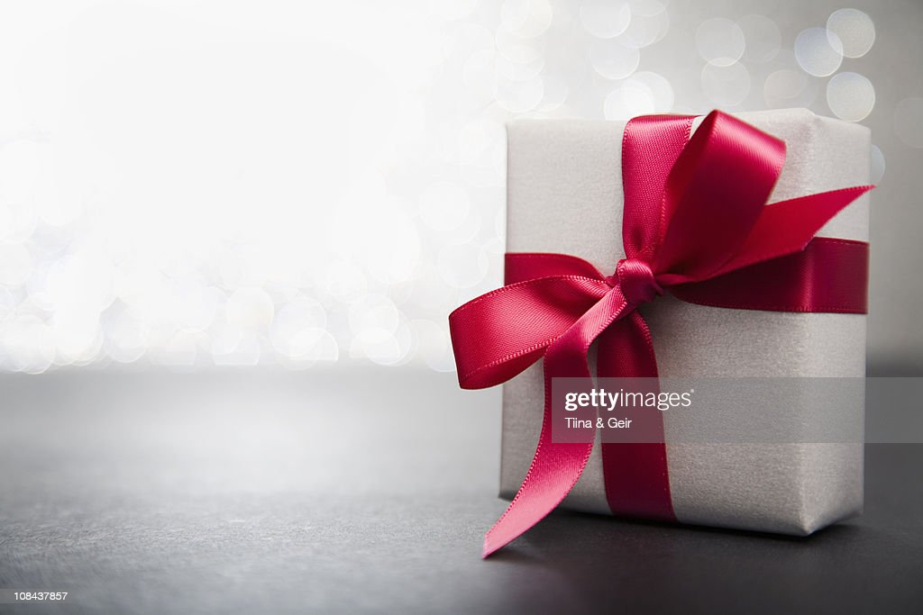Wrapped gift with red ribbon : Stock Photo