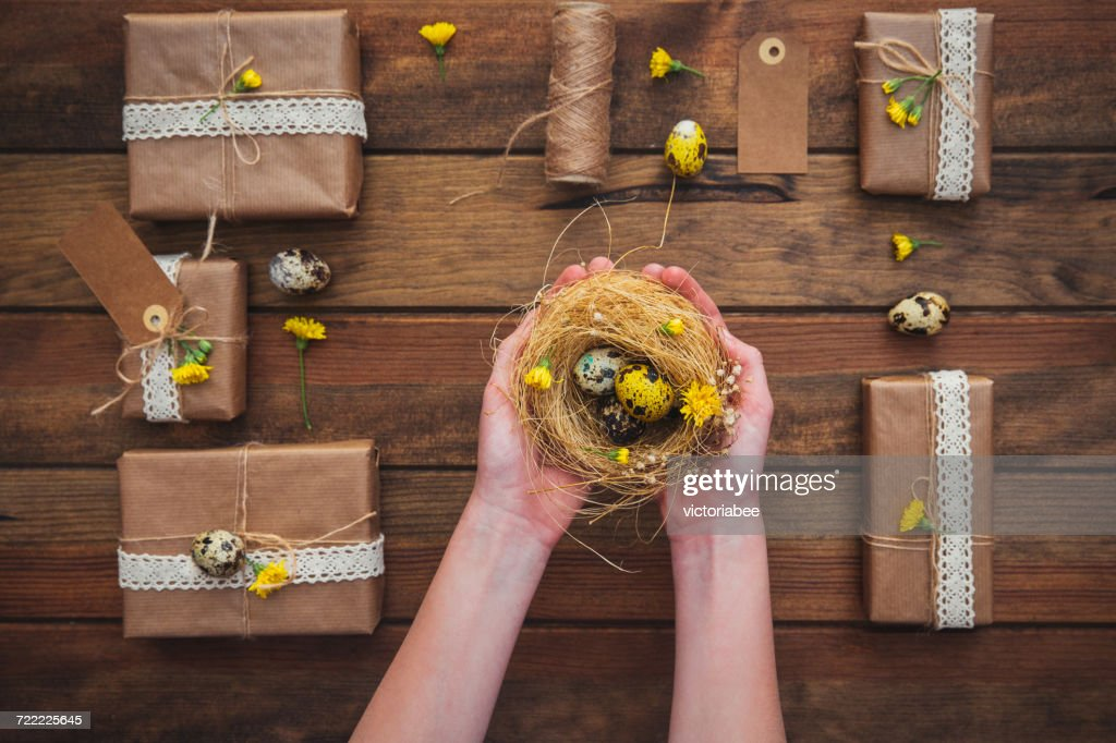 Wrapped gifts and girls hands holding a nest with easter eggs wrapped gifts and girls hands holding a nest with easter eggs stock photo negle Images