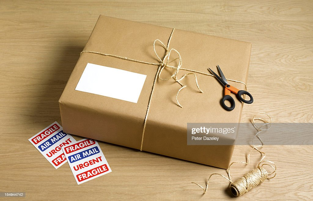Wrapped parcel with string, scissors and stickers : Stock Photo