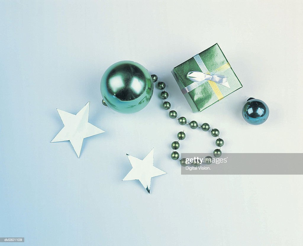 Wrapped present next to ornaments : Stock Photo