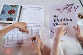 Close-up shot of unrecognizable couple wrapped up in planning wedding while sitting at table, man taking notes in calendar