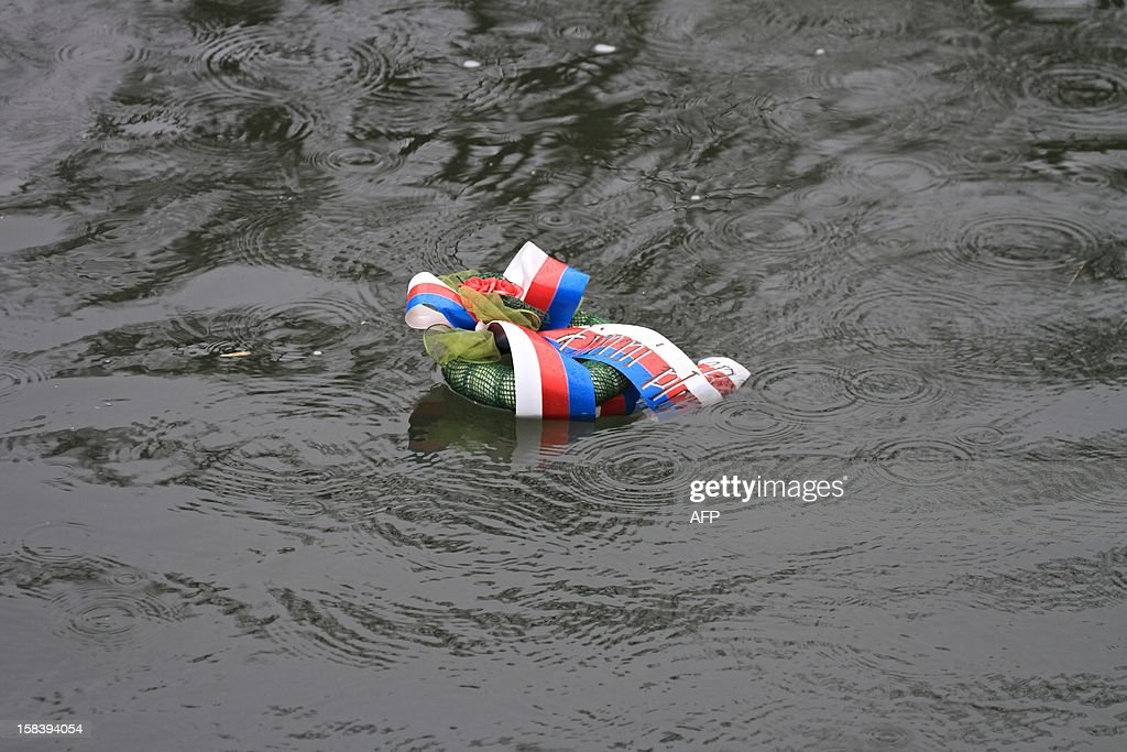 A wreath floats in the river Thaya near the border to Austria near Breclav, Czech Republic on December 15, 2012. Winter swimmers celebrated the entry of the Czech Republic to the Schengen area on December 21, 2007 and commemorated the victims shot by soldiers in crossing the border to Austria under communism. AFP PHOTO/ RADEK MICA