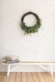Wreath hanging on white brick wall over bench at home.