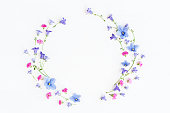 Wreath made of bell flowers, pansy flowers and pink flowers on white background. Flat lay, top view