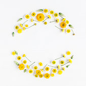Flowers composition. Wreath made of various yellow flowers on white background. Flat lay, top view