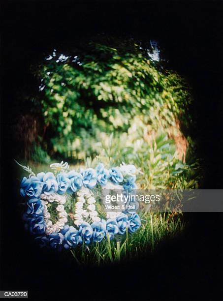 Wreath of flowers spelling 'Dad' in cemetery