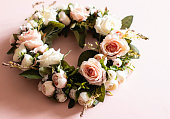 Close up of wreath of pink and white roses on a pink background - perfect for weddings or funerals