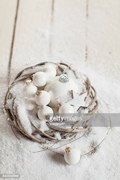 Wreath with white Christmas baubles, star and artificial snow on wood