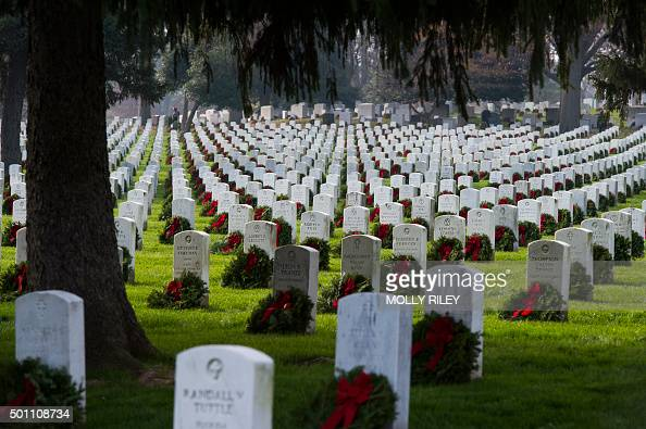 Wreaths are placed next to headstones during the 2015 National Wreaths Across America event at Arlington National Cemetery December 12 2015 in...