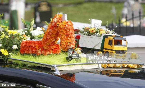 Wreaths in the shape of an earth mover and a truck on the hearse carrying the coffin of Paul Doherty at his funeral at St Mary's Church Clonmany in...