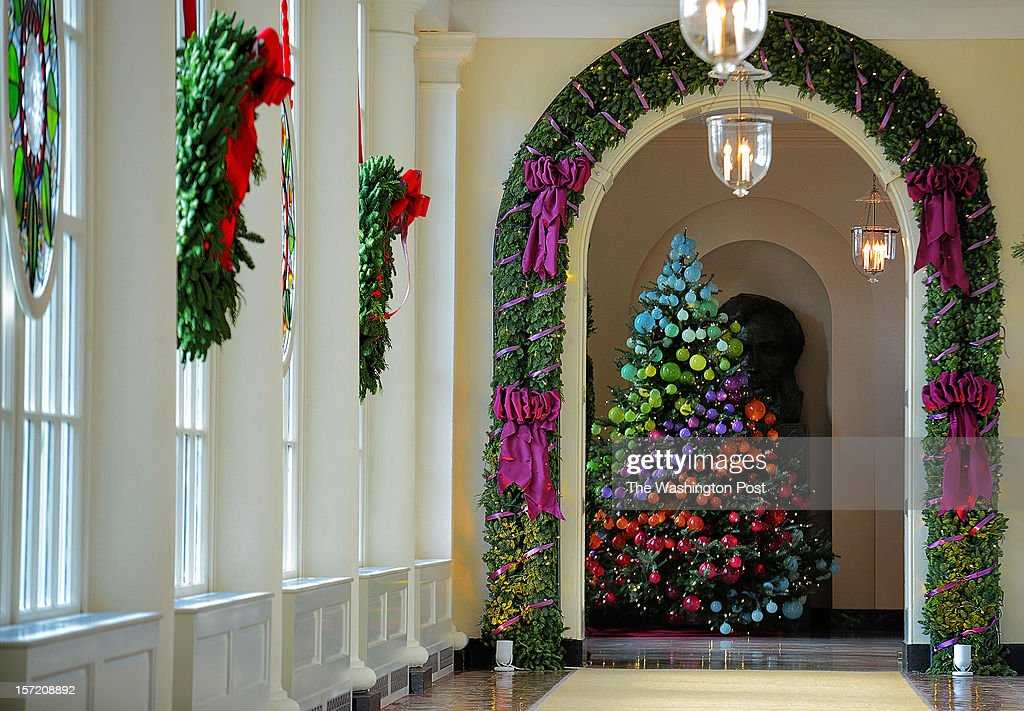 Wreaths of pine and stained glass cover windows in a long hallway leading to the East Garden room as the First Lady welcomes military families to share in this year's White House holiday decoration on November, 28, 2012 in Washington, DC.