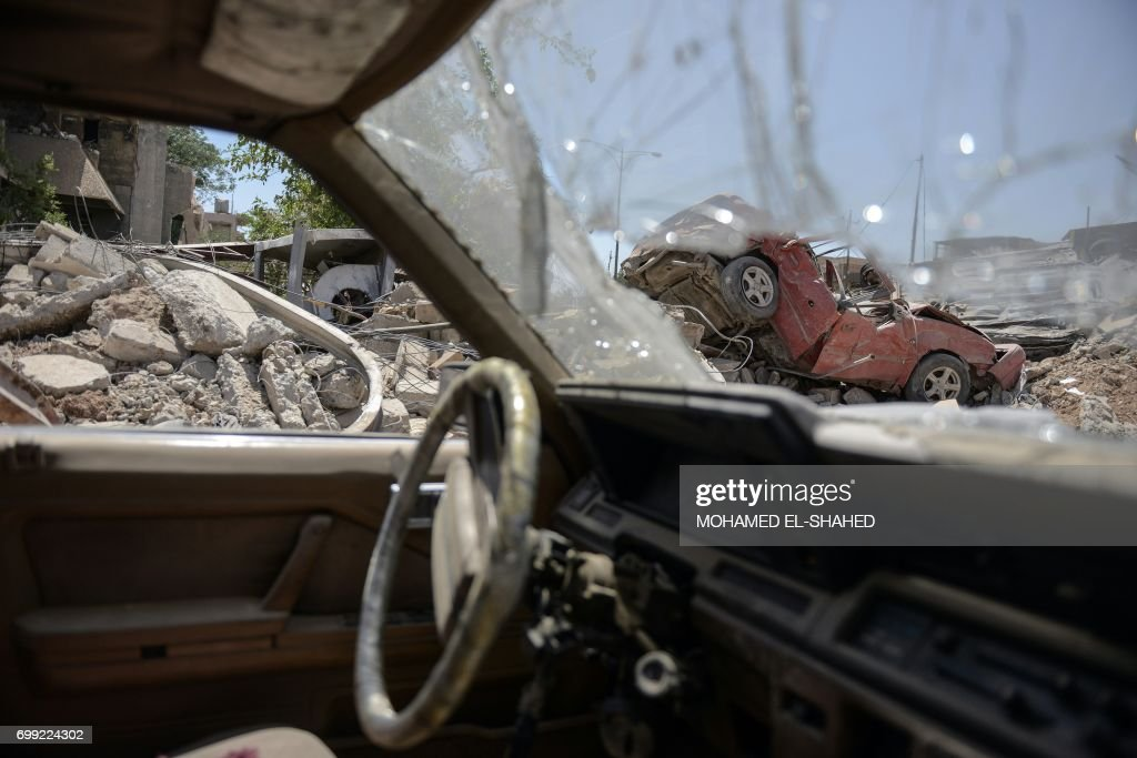 TOPSHOT - Wreckage of vehicles are seen near Mosul's Old City on June 21, 2017, during the ongoing offensive by Iraqi forces to retake the last district still held by the Islamic State (IS) group. /