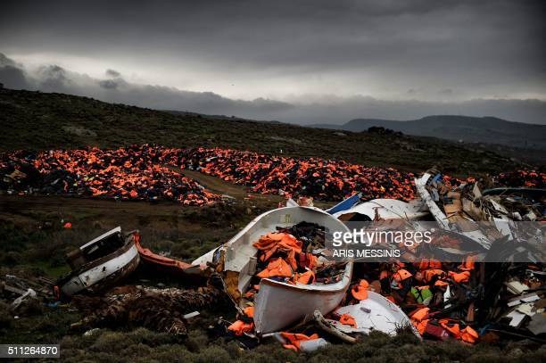 TOPSHOT Wrecked boats and thousands of life jackets used by refugees and migrants during their journey across the Aegean sea lie in a dump in...