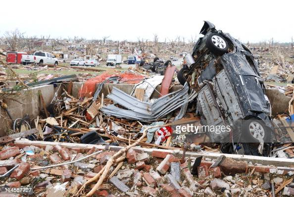 A wrecked car is seen in what appears to be the foundation of a house in tornado ravaged Joplin Missouri on Tuesday May 24 Rescuers combed through...