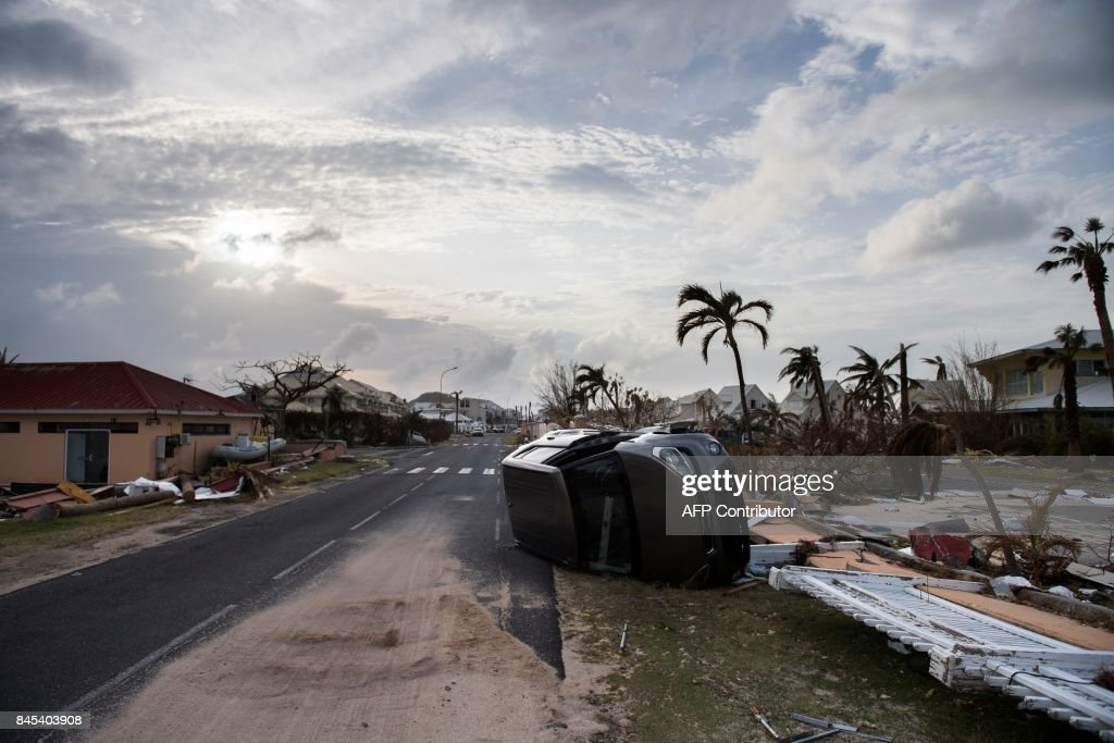 TOPSHOT - A wrecked car remains on the road of Baie Nettle area of Marigot, on September 10, 2017 on Saint-Martin island, devastated by Hurricane Irma. People on the islands of Saint Martin and Saint Barts turn to the colossal task of rebuilding after Hurricane Irma laid waste to their infrastructure and shattered their lives. / AFP PHOTO / Martin BUREAU