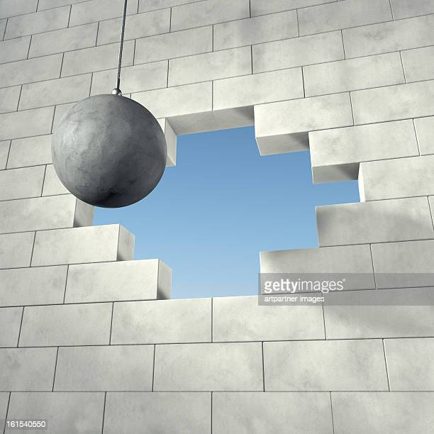 Wrecking ball on a brick wall with a hole