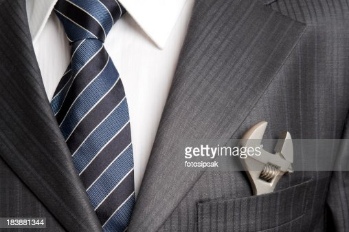 Wrench in pocket of businessman