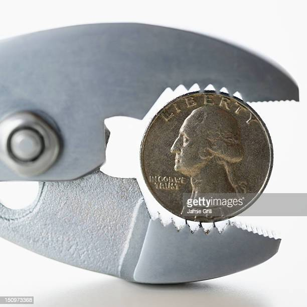 Wrench squeezing coin