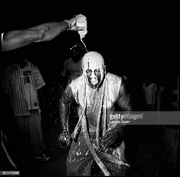 A wrestler getting splashed with sow as part of his preparation for a fight during a mbapat at Terrain Rouge in the Medina area of Dakar Senegal