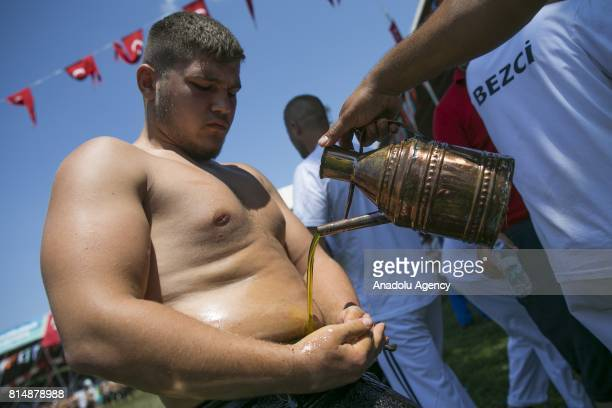 A wrestler is seen as he is being smeared olive oil over his body ahead of his competition during the 656th annual Kirkpinar Oil Wrestling Festival...