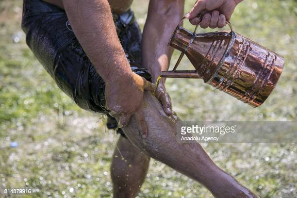 A wrestler is seen as he is being smeared olive oil over his leg ahead of his competition during the 656th annual Kirkpinar Oil Wrestling Festival in...