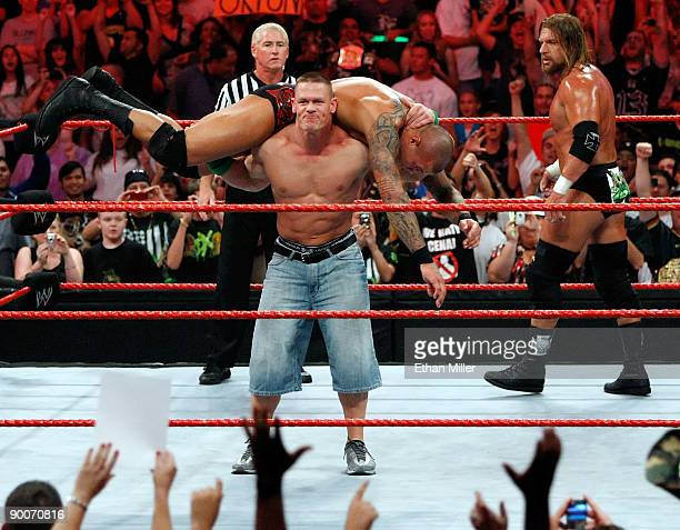 Wrestler John Cena picks up wrestler Randy Orton as wrestler Triple H looks on during the WWE Monday Night Raw show at the Thomas Mack Center August...
