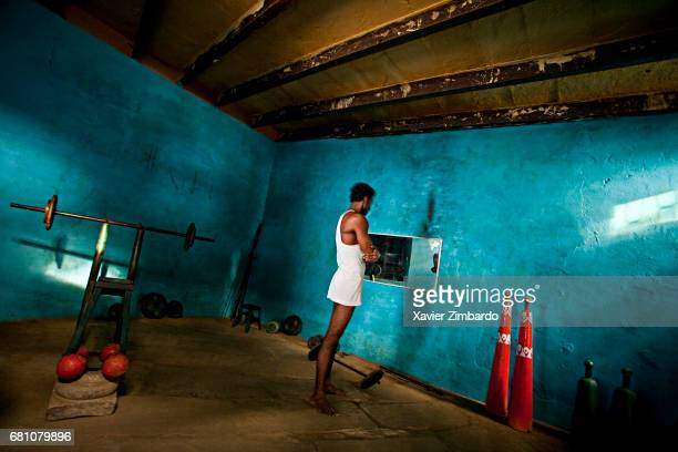 Wrestler looking at himself in a mirror while training during Kushti the ancient tradition of sacred Indian wrestling on October 28 2005 at Varanasi...