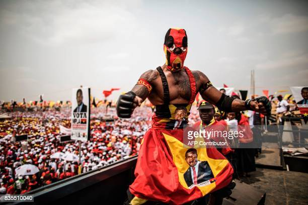 TOPSHOT A wrestler poses on top of a truck overlooking a crowd attending an electoral meeting by Angolan President and The People's Movement for the...