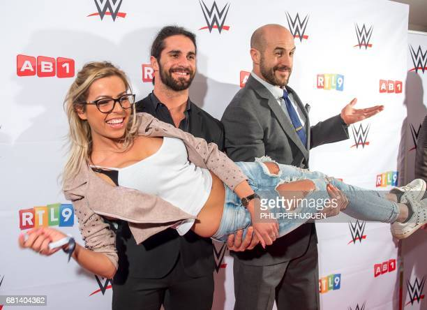 US wrestler Seth Rollins and Swiss wrestler Cesaro carry Hillary Aventurier contestant of French TV reality show ''Les Ch'tis'' as they pose before...