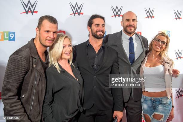 US wrestler Seth Rollins and Swiss wrestler Cesaro pose with Vincent Tressia and Hillary Aventurier contestants of French TV reality show ''Les...