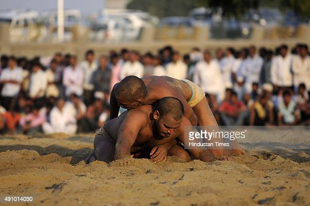 Wrestlers fight during Wrestling Title Championship at Gari Chaukhandi village on October 2 2015 in Noida India Thousands of wrestlers from different...
